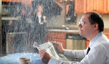 man sitting at table reading a newspaper with water raining on him