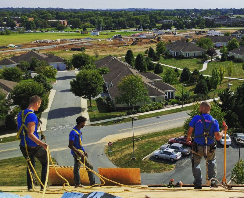 3 men wearing blue shirts on top of rood with rope and building materials