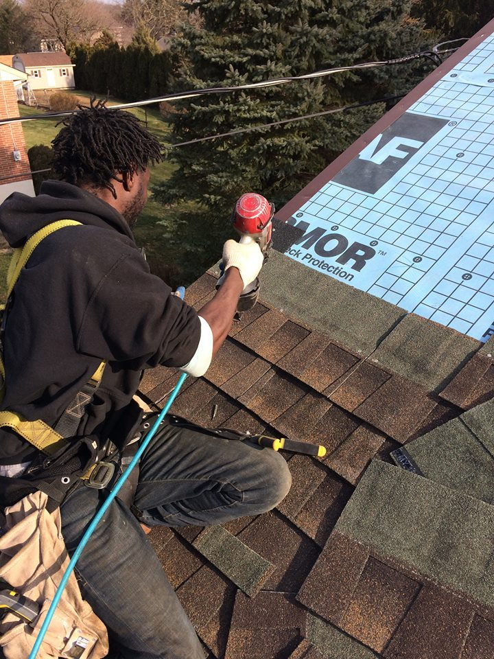 man with safety harness and equipment on roof