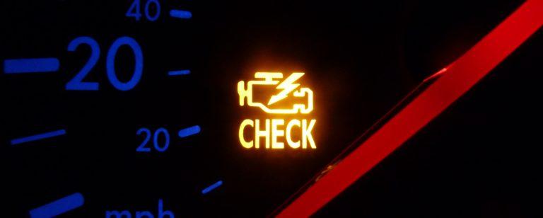 "lit ""check engine"" sign on car dashboard"