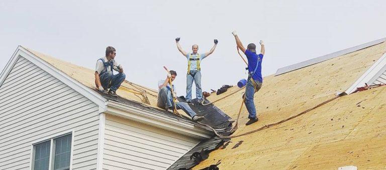 men cheering on top of roof