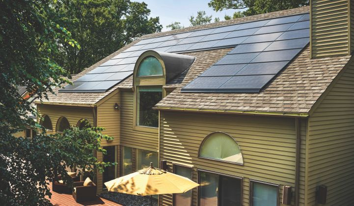 back of a tan house with decotech solar panels on the slanted roof
