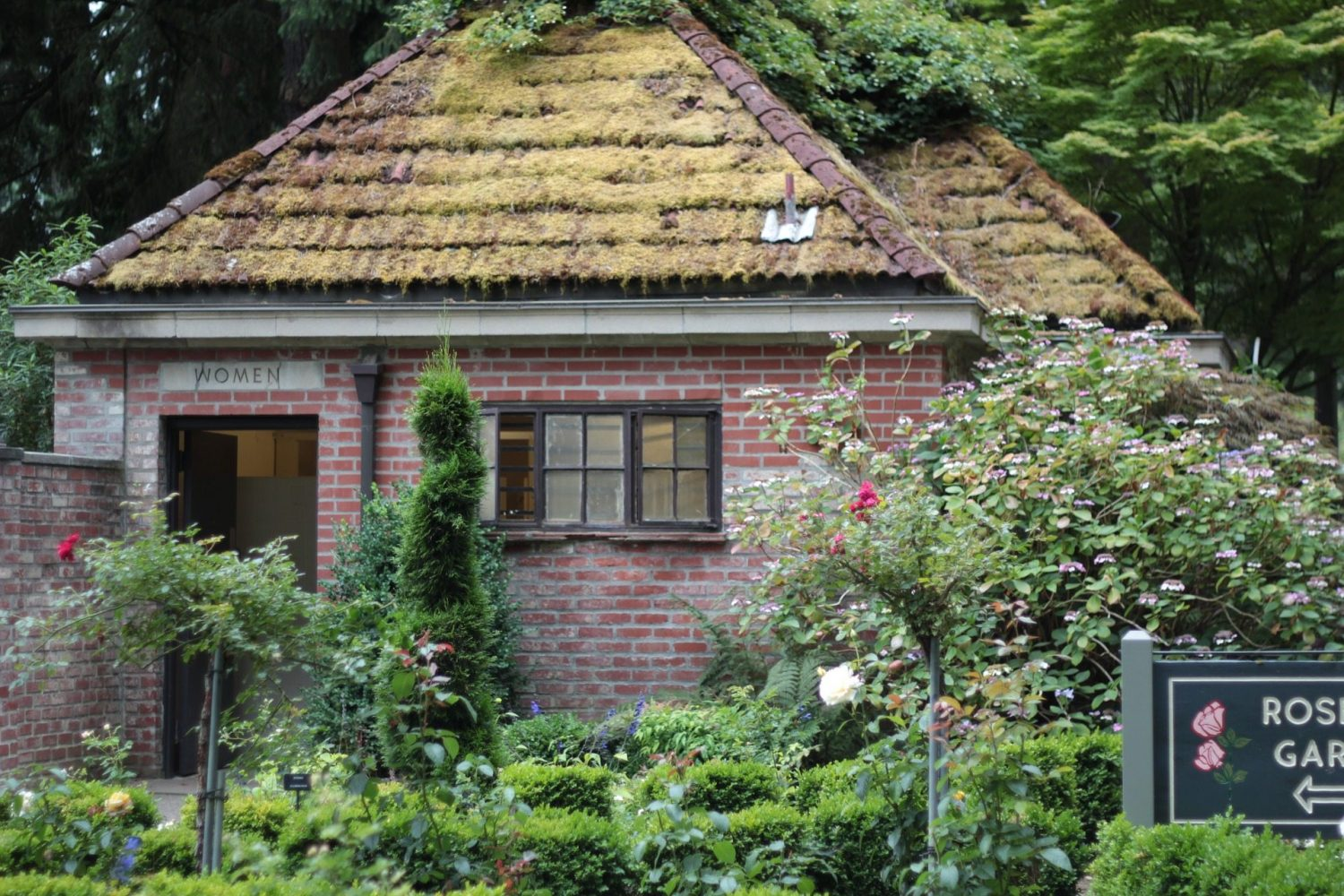 red brick bathroom building with moss on roof