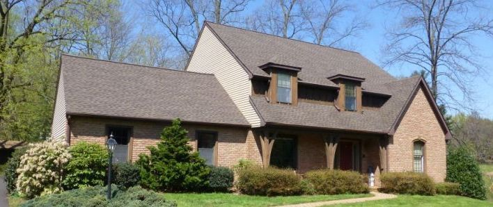 brick house with tress and bushes in the front yard