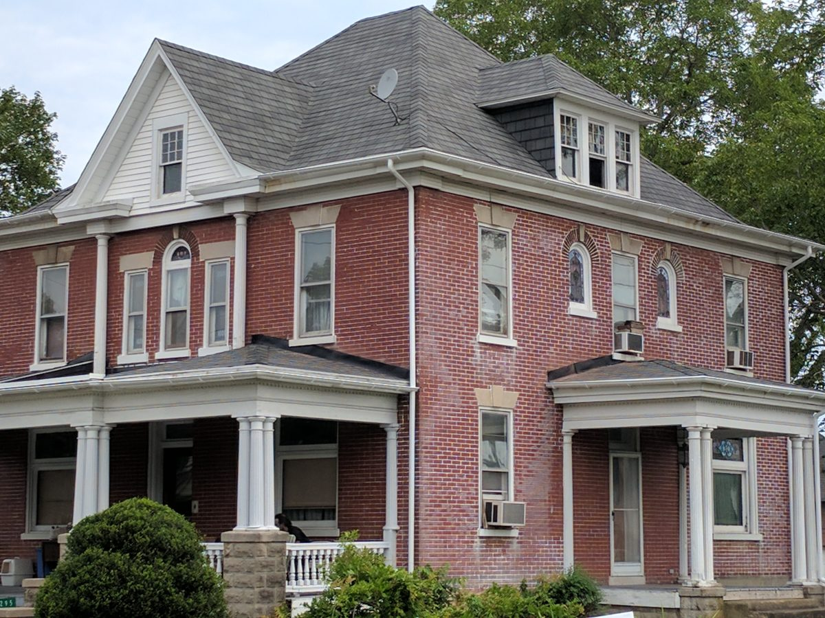 old 2-story red brick house with gray roofing