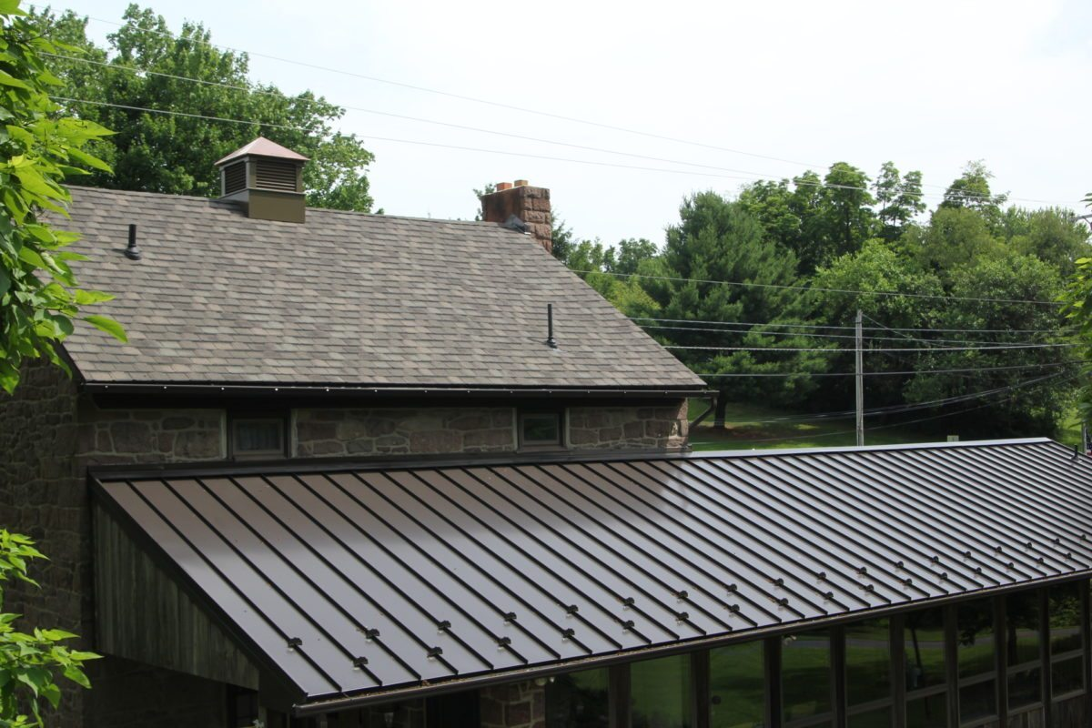 brown metal roof next to a building with non-metal roof