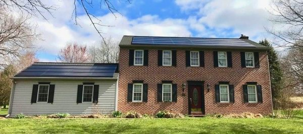 tan and red brick house with Decotech solar panels on roof