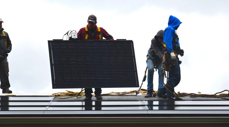 4 men on a roof installing Decotech solar panels