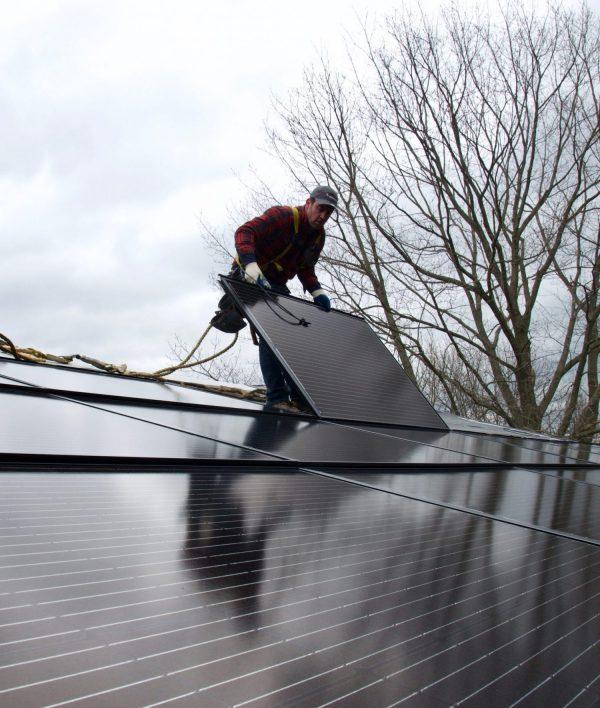 man on roof installing Decotech solar panel system