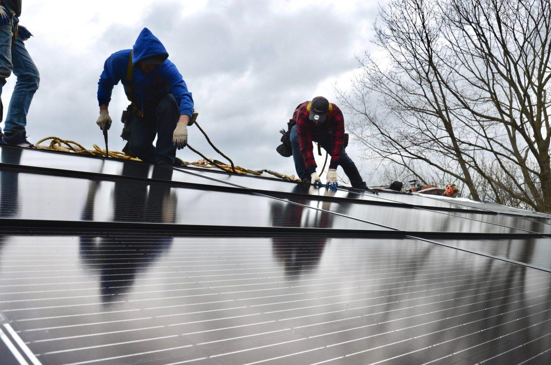 3 men on a roof securing Decotech solar panels