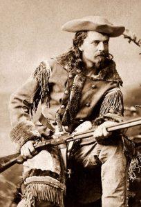 Buffalo Bill sitting down holding a shotgun
