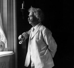 Mark Twain in a suit holding a pipe looking out a window
