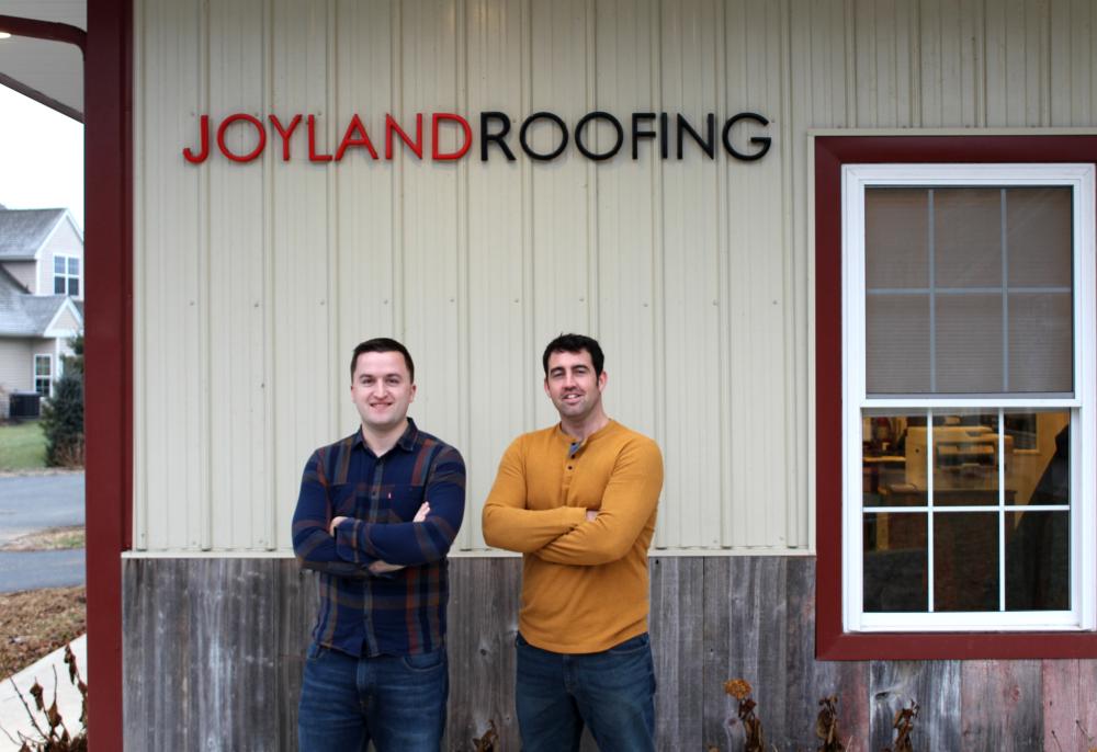 2 men standing in front of Joyland Roofing building