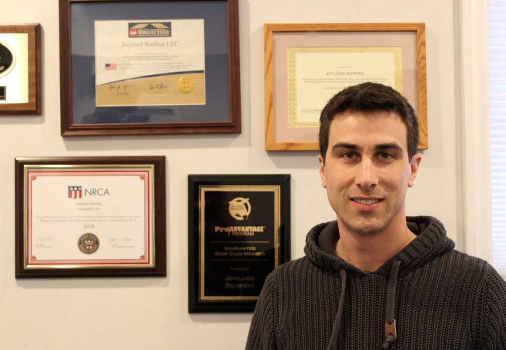 Man standing in front of wall with frames of awards and certifications