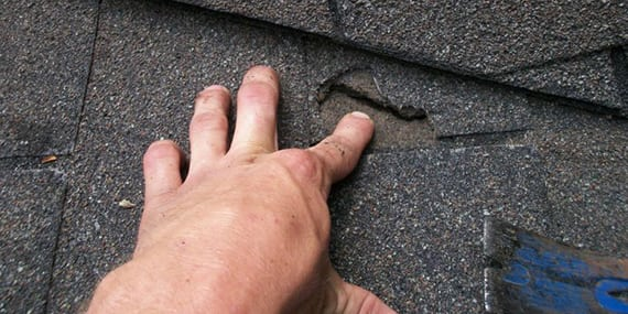hand pointing to roof damage from storm