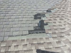 asphalt shingles are blown off from a commercial building