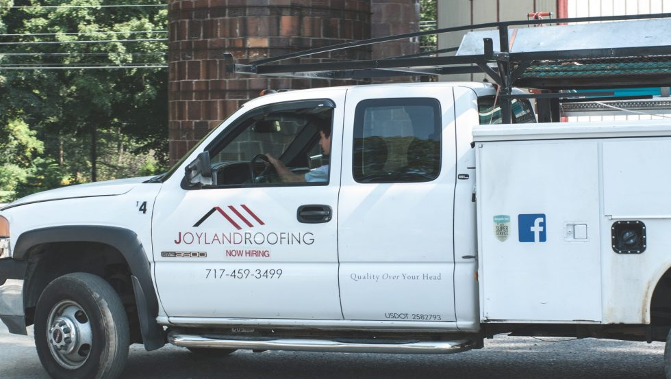 man white Joyland Roofing truck with window down