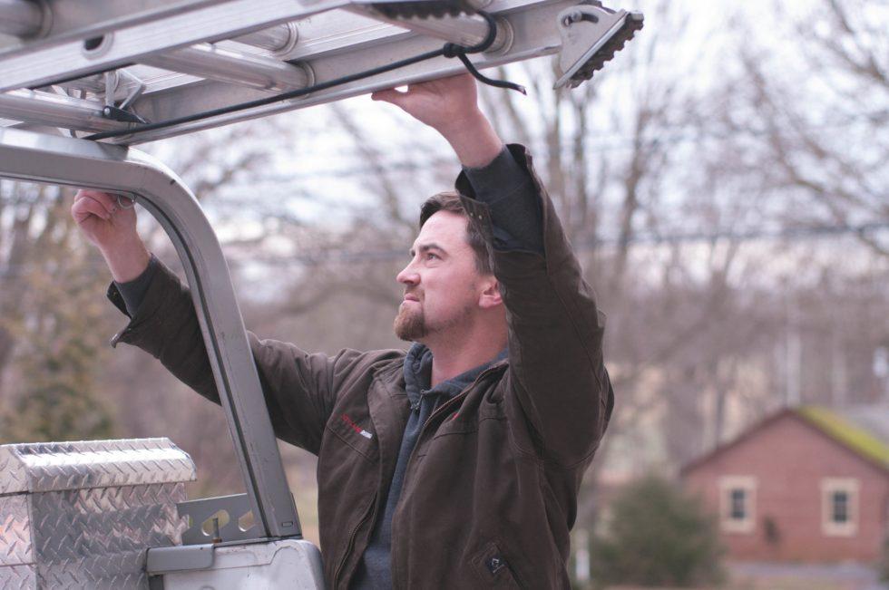 man grabbing ladder on top of truck