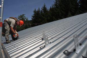 man on roof installing corrugated metal panels