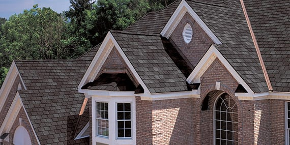 brick 2-story house with asphalt shingle roofing
