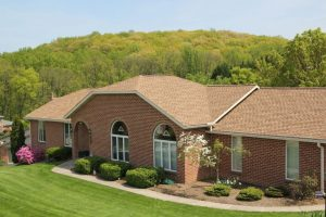 brick house in front of forest with shake asphalt shingles on roof