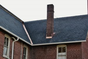 red brick house with chimney on dark slanted roof