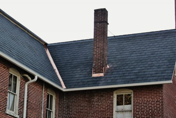 red brick house with dark slanted roof and red brick chimney