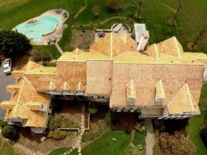 overview of a house with wooden roofing and a pool in backyard