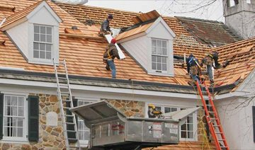 4 people using ladders to climb up on roof to install wood roofing