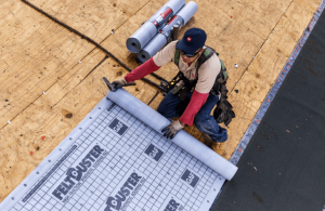 person on roof laying down the synthetic underlayment material