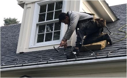 Man on roof holding hammer