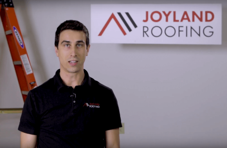 Man standing in front of Joyland Roofing sign