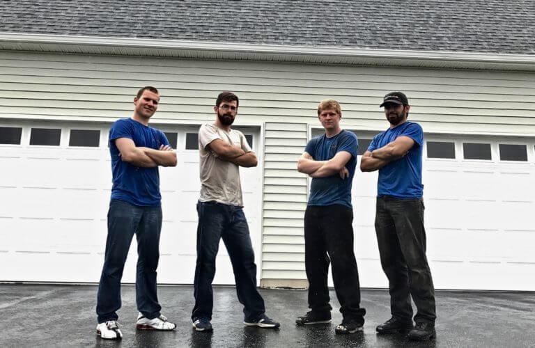 4 men standing in front of two white garage doors